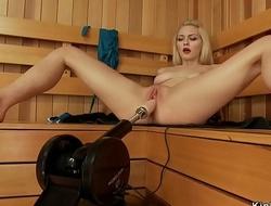 Shaved blonde fucks machine in sauna